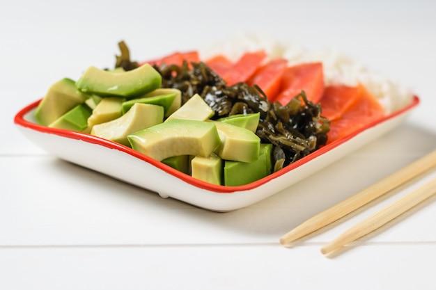 Tigela com arroz, algas, fatias de abacate e peixe em uma mesa branca com varas de madeira.
