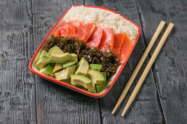 Tigela com arroz, algas, fatias de abacate e peixe em uma mesa preta com varas de madeira.