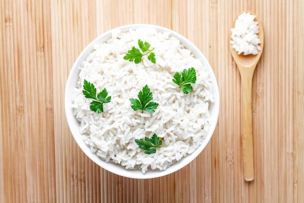 Tigela com arroz cozido branco com salsa fresca verde para delicioso almoço saudável. cereais e pratos.