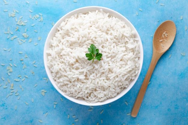 Tigela com arroz cozido branco com salsa fresca verde para delicioso almoço saudável em um surfce azul