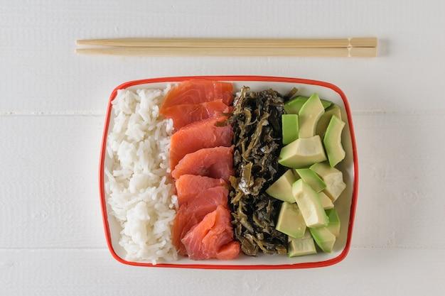 Tigela com arroz de grãos longos, algas, fatias de abacate, salmão e palitos de madeira em uma mesa de madeira branca. a vista do topo.