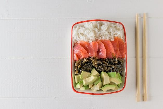 Tigela com arroz de grãos longos, algas, fatias de abacate, salmão e palitos de madeira sobre uma mesa branca clara. a vista do topo.