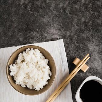 Tigela com arroz no guardanapo perto de pauzinhos e molho de soja