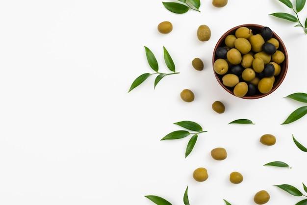 Tigela com azeitonas e folhas de propagação e azeitonas