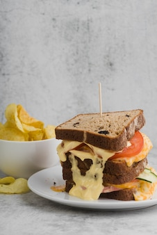 Tigela com batatas fritas ao lado de sanduíche