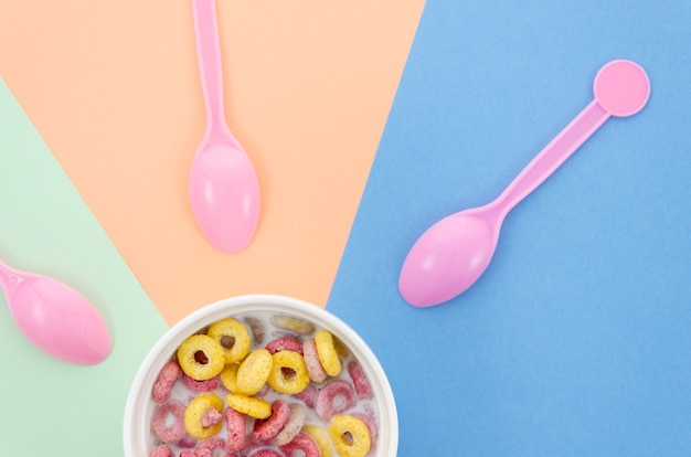 Tigela com cereais e rosa fofos colheres