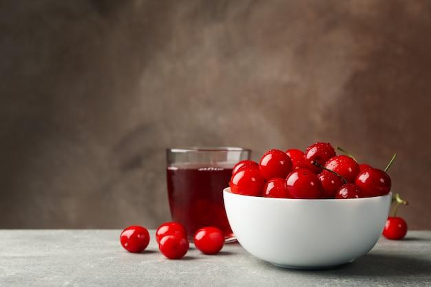 Tigela com cereja vermelha e copo de suco na mesa cinza