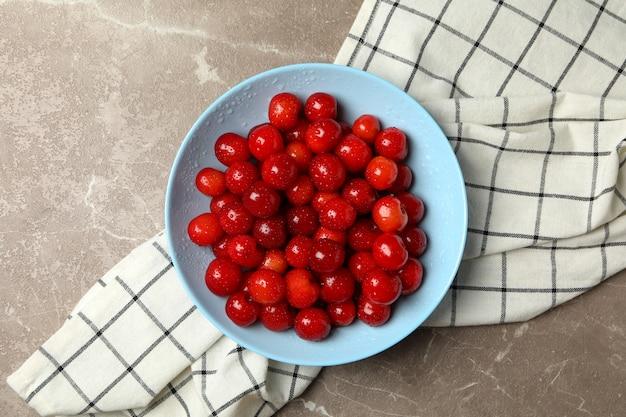 Tigela com cereja vermelha e toalha em fundo cinza