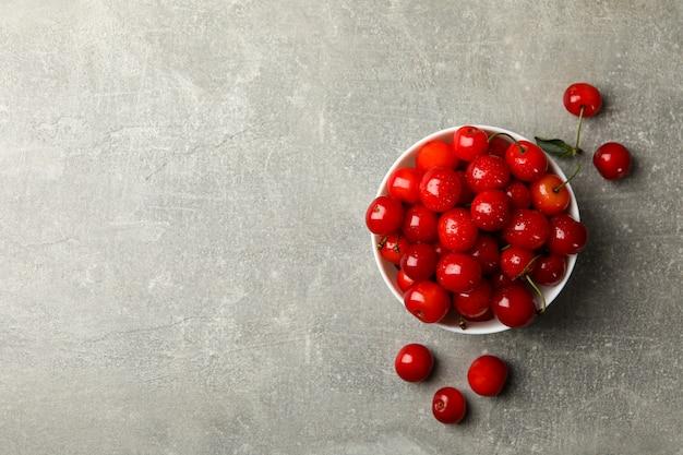 Tigela com cereja vermelha em fundo cinza