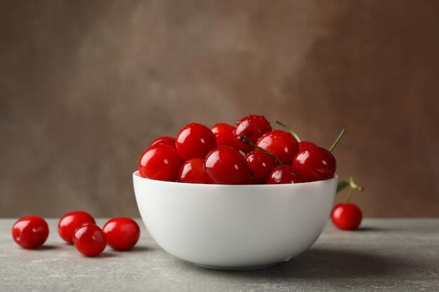 Tigela com cereja vermelha na mesa cinza