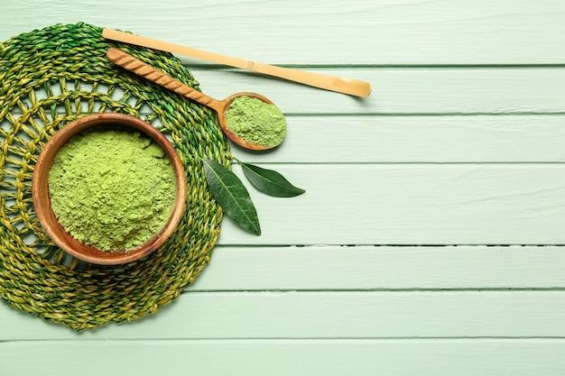 Tigela com chá matcha em pó, chashaku e colher na cor de fundo de madeira