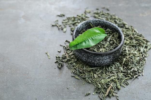 Tigela com chá verde seco em superfície escura