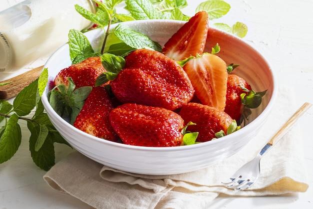 Tigela com deliciosos morangos grandes (fresones), frescos, inteiros, recém cortados, com leite e com hortelã-pimenta
