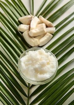 Tigela com esfoliante corporal de coco e folha de palmeira no fundo branco