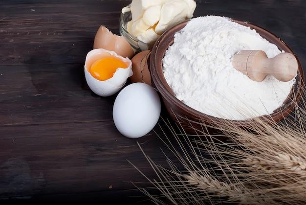 Tigela com farinha ovos espigas de trigo e manteiga no conceito de comida e bebida de tábua de madeira vintage