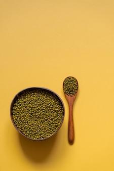 Tigela com feijão mungo em um fundo amarelo. comida ecológica, pratos ecológicos.