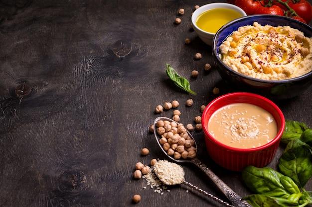 Tigela com homus, grão de bico, tahine, azeite, sementes de gergelim, tomate cereja e ervas no fundo escuro de madeira rústico.