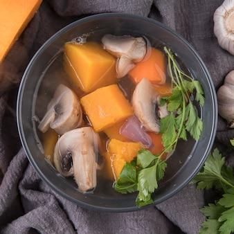 Tigela com ingredientes da sopa e caldo close-up