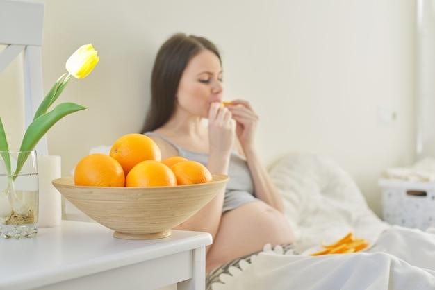 Tigela com laranjas em foco, jovem grávida comendo fatias de laranjas sentada na cama