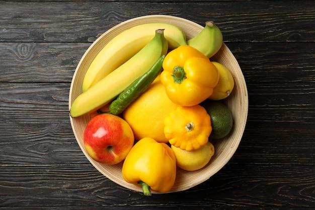 Tigela com legumes e frutas em fundo de madeira