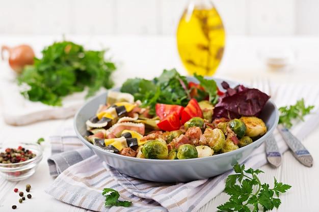 Tigela com macarrão farfalle, couve de bruxelas com bacon e salada de legumes frescos