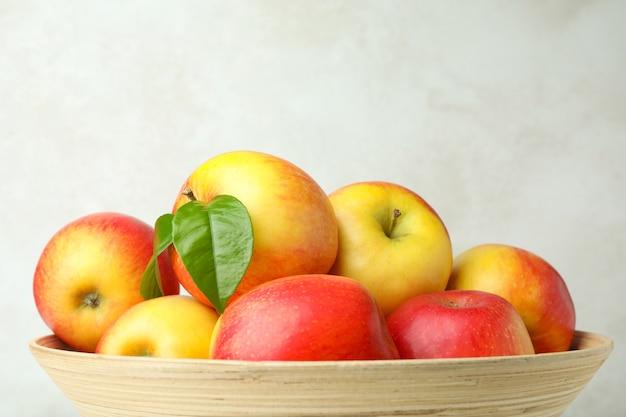Tigela com maçãs vermelhas em plano de fundo texturizado branco, close-up