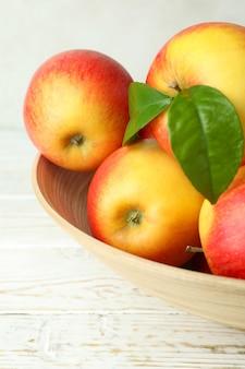 Tigela com maçãs vermelhas na mesa de madeira branca