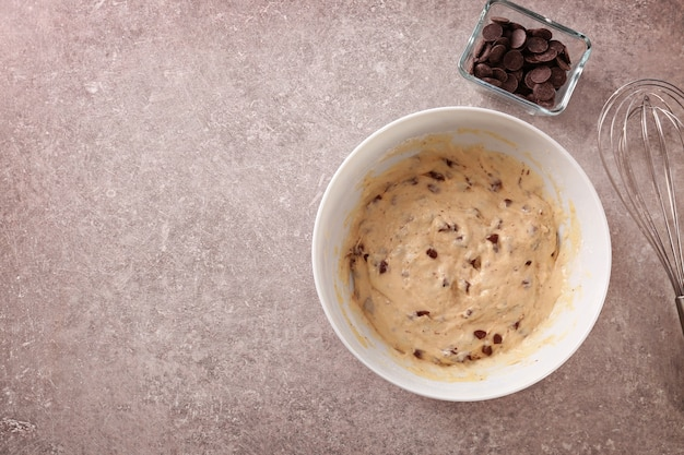 Tigela com massa crua e gotas de chocolate na mesa da cozinha
