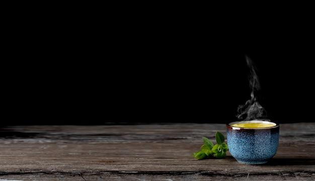 Tigela com matcha chá verde em uma mesa de madeira vintage