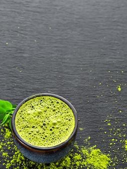 Tigela com matcha de chá verde, ao lado de folhas de chá e pó de chá em uma mesa de pedra preta