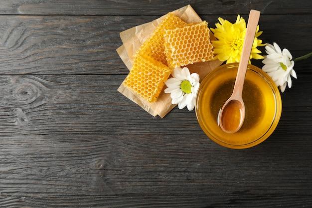 Tigela com mel, favos de mel e flores sobre fundo de madeira