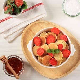 Tigela com minúsculos cereais panqueca com morangos e folhas de hortelã em um fundo branco. e placa de madeira. comida da moda. mini panquecas de cereais. orientação retrato