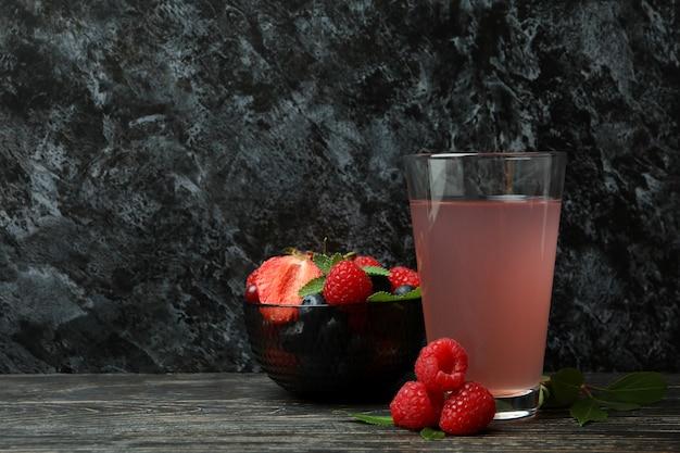 Tigela com mistura de frutas vermelhas e suco na mesa de madeira