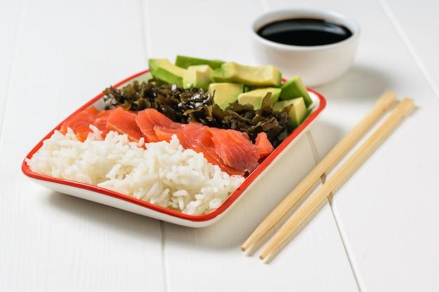Tigela com molho de soja e salada de abacate, arroz, algas e peixes na mesa branca. cozinha mediterrânea
