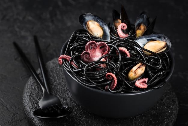 Tigela com passado preto e frutos do mar