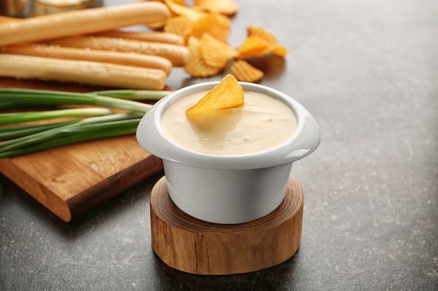 Tigela com pasta de queijo e batata frita em suporte de madeira