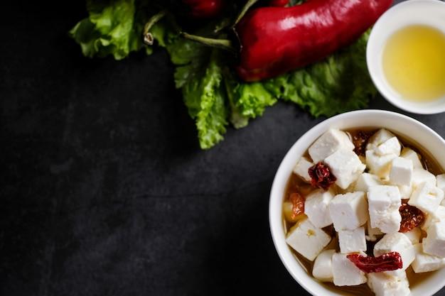 Tigela com pedaços de queijo feta e tomates secos e óleo, vista superior com copyspace