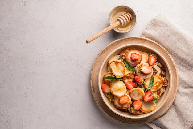 Tigela com pequenas panquecas de cereais com morangos, hortelã e mel em um fundo cinza de concreto