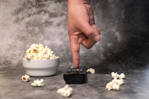 Tigela com pipoca, a mão do homem com o controle remoto da tv em fundo escuro. assistir séries ou filmes e comer pipoca