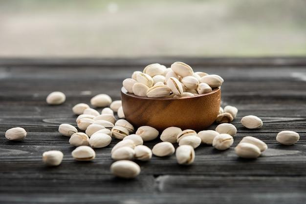 Tigela com pistache em uma mesa de madeira.
