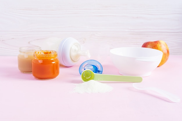 Tigela com purê de legumes e garrafa de comida para bebê no fundo rosa