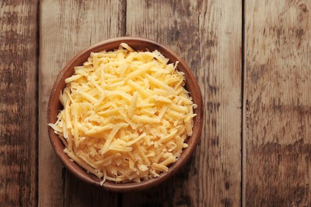 Tigela com queijo ralado em fundo de madeira