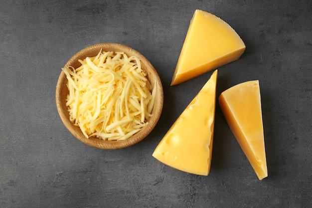 Tigela com queijo ralado em fundo escuro