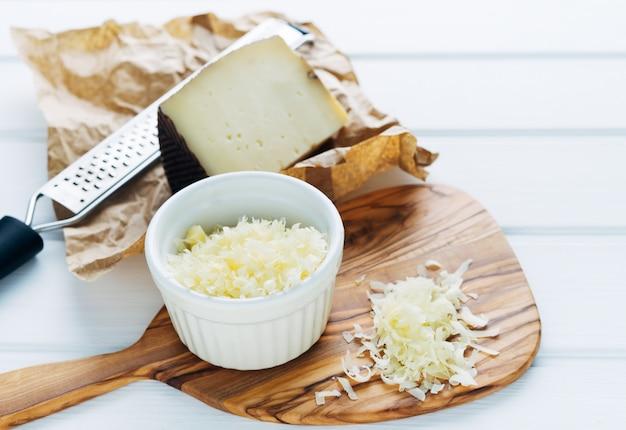 Tigela com queijo ralado em uma tábua. pedaço de queijo e ralador. copie o espaço.