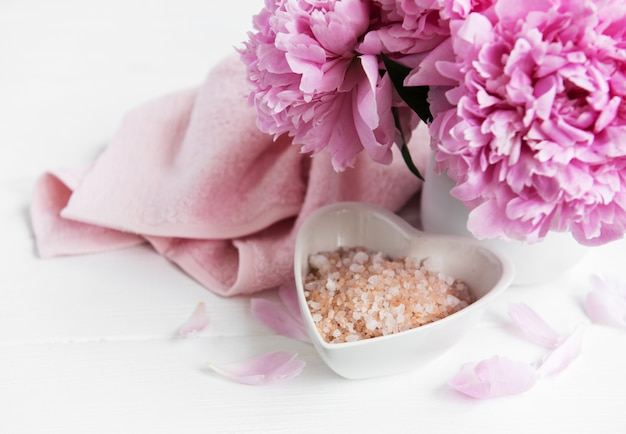 Tigela com sal marinho, toalhas macias e flores de peônia
