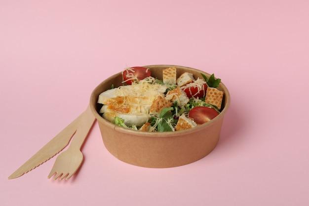 Tigela com salada caesar e talheres em fundo rosa