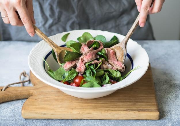 Tigela com salada de espinafre, cebola, tomate cereja, fatias de bife e especiarias. mulher, mexe salada, com, colheres madeira