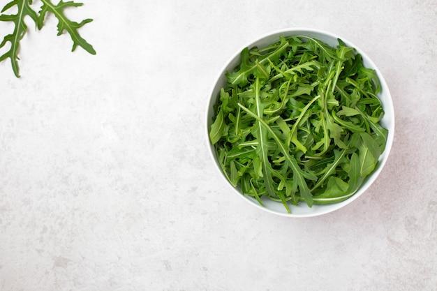 Tigela com salada de rúcula de rúcula verde fresca e saudável em superfície cinza claro