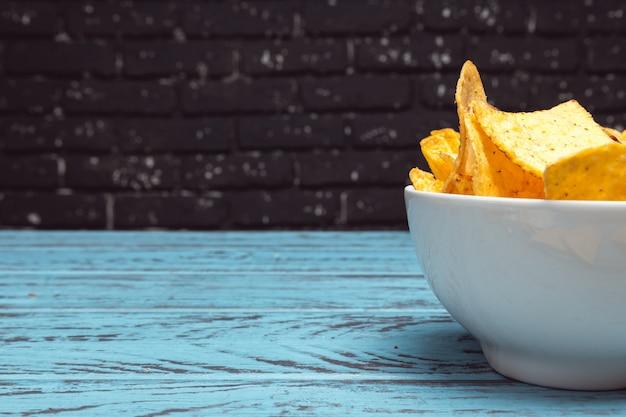 Tigela com salgadinhos, batatas fritas close-up no fundo escuro de tijolos