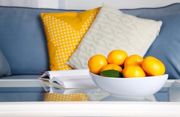Tigela com tangerinas frescas na mesa da sala de estar, close-up